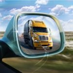 a yellow semi truck is show in the passenger mirror of another vehicle