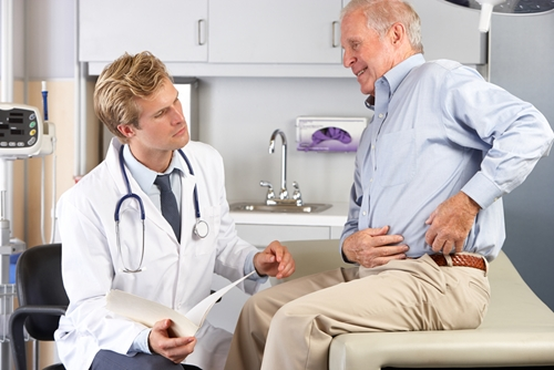 a concerned doctor looks as an elderly man points to his abdomen in a doctors office