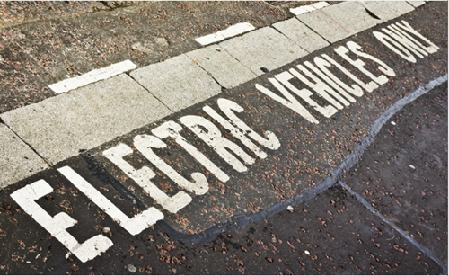 "A notice saying ""ELECTRIC VEHICLES ONLY"" painted on the ground"