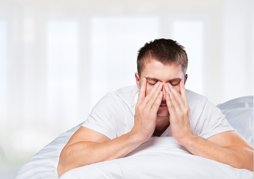 A tired man rubbing his face as he lays in bed