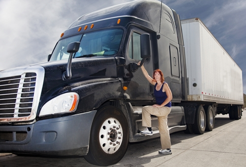 A woman stands perched on the foot landing of the cab of her semi truck.