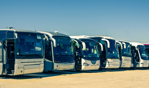 a fleet of buses parked very close to one another
