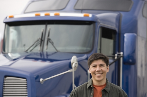 young man stands smiling in front of a blue freight truck